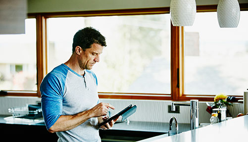 Man in Kitchen browsing on an iPad